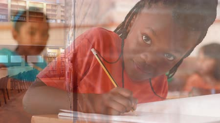 scolari : Digital composite of little African-American girl working in a class room surrounded by animation of library. She is smiling and looking at camera Filmati Stock