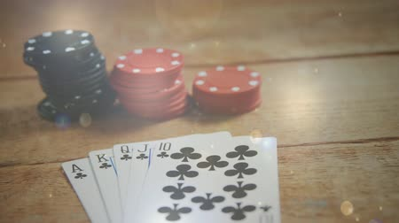 croupier : Digital composite of poker cards and chips on a wooden table against glitters Stock Footage
