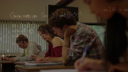 high school : Digital composite of serious high school class with mathematics symbols in foreground Stock Footage