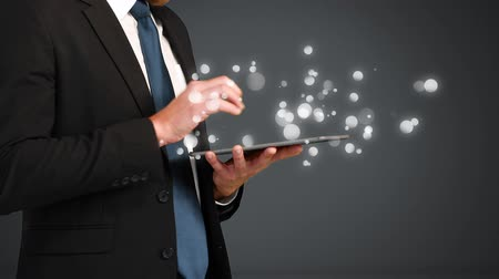 görgetés : Digital composite of a businessman using a digital tablet with his hand surrounded by white bubbles on a grey background.