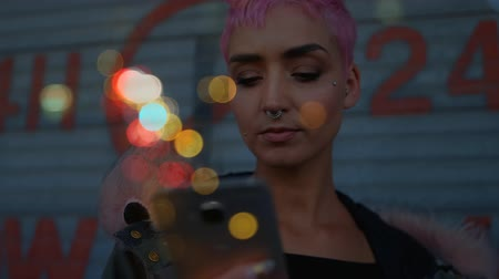 pronikavý : Digital composite of a pink-haired woman using her mobile phone standing in the street surrounded by a bokeh effect.