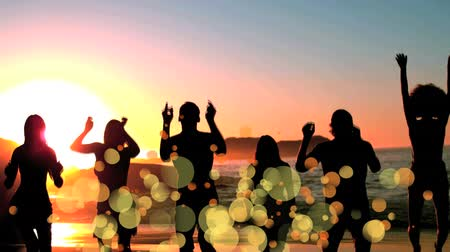 soma : Digital composite of happy friends jumping on the beach at sunset surrounded by yellow bokeh effect