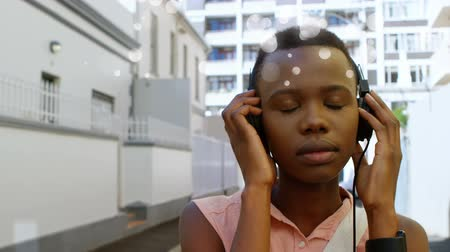 ausgrenzung : Digital animation of beautiful African-american listening music with headphone on street in the city with light bubble in animation
