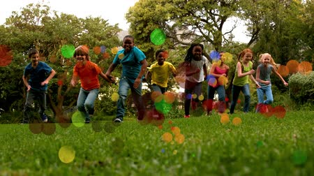 草 : Low angle view of school kids running in slow motion towards the camera in a park with light bubble in foreground