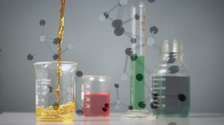 banka : Digital composite of a beaker being filled by a yellow liquid beside another beaker, a graduated cylinder, and a flask and molecule models falls in the background. Dostupné videozáznamy