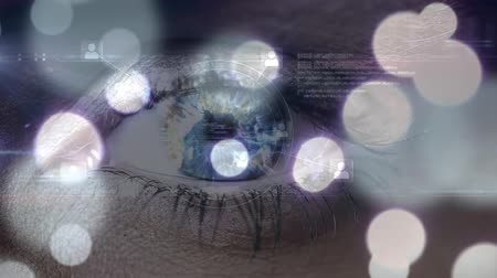 выигрыш : Digital composite of an adult female eye while data glows on the screen and bokeh falls in the foreground Стоковые видеозаписи