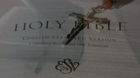 evangelical : Digital composite of the holy bible being opened and the crucifix falling Stock Footage