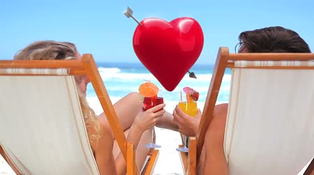 amor : Digital composite of caucasian couple by the beach celebrating with a toast while a heart floats between them