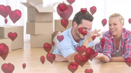 údiv : Digital composite of caucasian couple on the floor unpacking boxes and man giving the keys to wife. Red hearts floating on the screen Dostupné videozáznamy