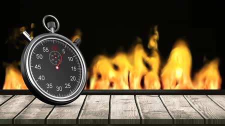 stoper : Digitally generated black stop watch with moving hands on a wooden plank in background of burning fire
