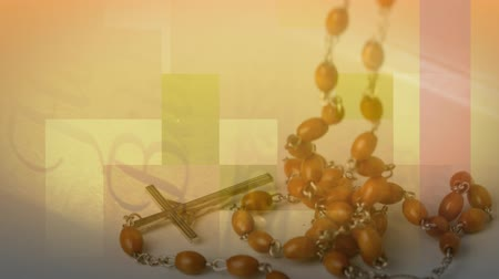 sagrado : Digital composite of a rosary falling. Background in an orange shade with candles