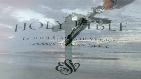el yazması : Digital composite of the holy bible with crucifix. background shows the sky with clouds Stok Video