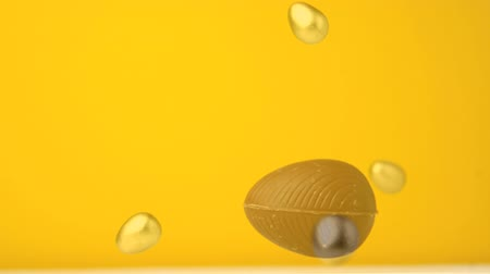 vasárnap : Digital composite of easter eggs falling against a yellow background