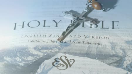 evangélium : Front view of the holy bible with crucifix. Background of snowy mountains.