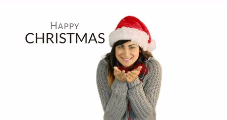 knitted : Woman wearing knitted clothes and a Christmas hat smiles and blows a kiss with a Christmas greeting text beside her 4k