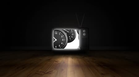 punctuality : Digital animation of a television turning on to reveal clocks on its screen. The television in on the floor in a dark empty room