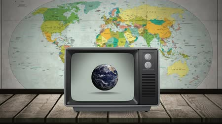 changing channel : Digital animation of a television on top of a wooden plank table with a rotating globe on its screen. A world map is seen behind the television as a background Stock Footage