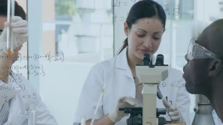 forensic : Close up view of a multiracial group of scientists conducting research in a lab with equations floating in the foreground Stock Footage