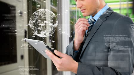 kifinomult : Side angle of a Caucasian businessman studying on his tablet with a digital image of a globe slowly rotating just above his tablet Stock mozgókép