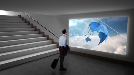 kifinomult : Rear view of a Caucasian businessman walking in the hall way paused to look at a screen near the stairs. The screen is projecting a digital animation of a rotating globe