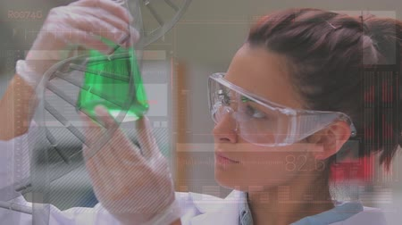 banka : Close up of a female Caucasian scientist studying a green liquid in a flask. The clip has a semi transparent DNA stand effect on the foreground
