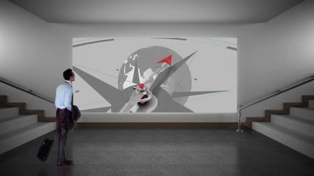 bússola : Businessman walking on the stairs paused to gaze at a screen on the wall. The screen is playing a clip of a compass pointing to a rotating globe