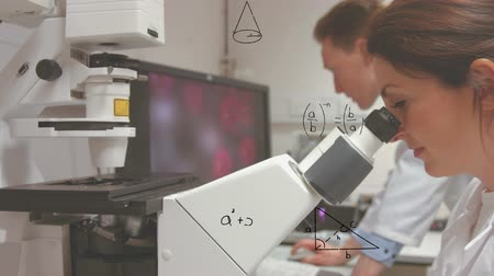biotechnologia : Close up side view of a Caucasian female scientist studying on the microscope with equations floating on the foreground. Another male scientist is seen in the background on the computer