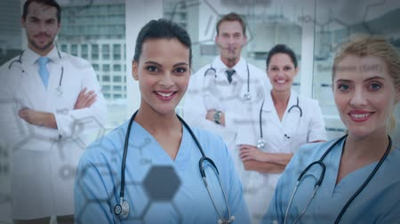take blood : Close up multiracial medical team standing in the office smiling and arms crossed. Digital animation of equations and graphs are running in the foreground