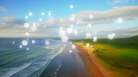 높은 각도 : High angle of a beach shore with clear skies. Digital spherical lights are running in the foreground 무비클립