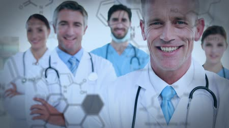 internar : Close up of a group of doctors and nurses smiling at the camera with their arms crossed. The foreground is filled with chemical equations