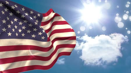 nationality : Close up of the american flag waving under the bright sunny sky with bokeh lights Stock Footage