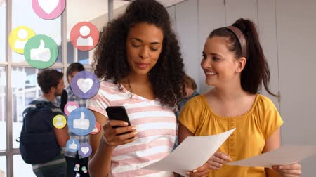 afstuderen : Front view of a Black and a Caucasian girl in a hallway with other two male students talking in the background. They are texting while holding a piece of paper. Digital animation of social media icons are flying up in the foreground