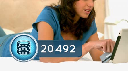 monety : Close up of a Hispanic woman laying in bed while checking her tablet. beside her is an animation of a coins icon inside a blue count bar with increasing number count.
