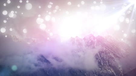 celestial : High angle of a mountain peek with bright shining lights from the sky. bokeh of light effects are in the foreground