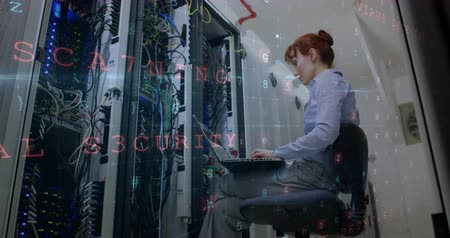 baixo ângulo : Low-angle view of a Caucasian woman working on a laptop inside the server room, with warning of cyber attack from a computer screen. 4k