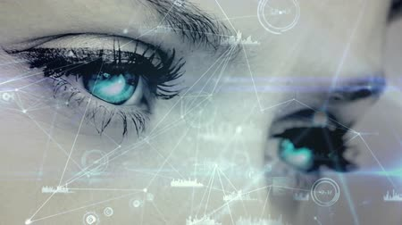 Focused view of blinking woman eyes looking at the screen with rotating blockchain connections and bar charts Stock Footage