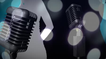 wizualizacja : Digital animation of a close-up view of a silhouette of a dancing woman with headset on the right, and a half-body view of a silhouette of a dancing woman on the left. Two separate views of vintage microphones and moving glowing white circles on foregroun