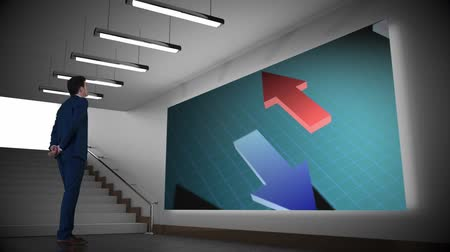 kifinomult : Digital animation of a businessman in suit watching black, blue and red arrow icons moving in opposite directions from a grid screen inside an office building.