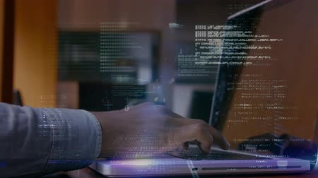 sofistike : Digital composite of businessman using laptop while binary codes move on the foreground in office Stok Video