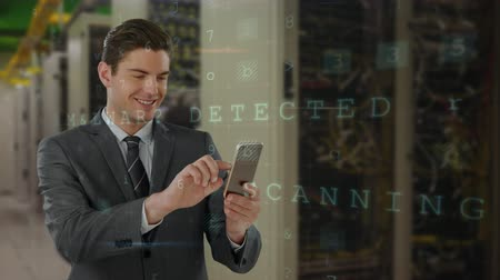 adminisztrátor : Digital composite of young Caucasian male executive using mobile phone while standing in server room and binary codes moving on the foreground. Stock mozgókép