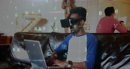 フォアグラウンド : Digital composite of an African-american man wearing a virtual reality headset while typing on his laptop and codes running in the foreground 4k