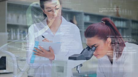 geny : Digital composite of two female Caucasian in a lab and a foreground with a DNA helix and interface codes. One of the scientists write notes while the other peeks at a microscope
