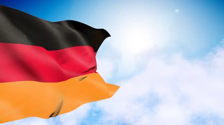 Октоберфест : Digital animation of a German flag waving against a blue sky background Стоковые видеозаписи