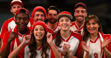 beisebol : Front view of sports fans, wearing white and red jerseys, cheering as a group. 4k