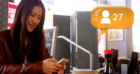 follower : Close up of beautiful Asian woman typing on mobile phone while sitting at restaurant. Digital animation of message bubble with follower icon and number count up 4k
