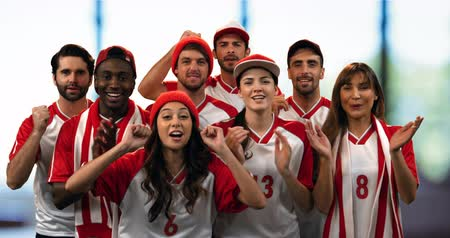 gradins : Front view of a group of sports fans wearing red and white jerseys cheering loudly 4k