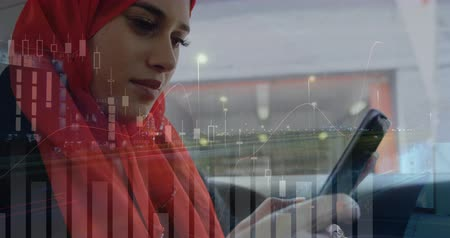 выигрыш : Close up of a Muslim woman wearing a hijab typing on her phone while riding in a moving vehicle. Digital animation of graphs and statistics are running in the foreground 4k