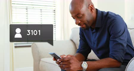 follower : Side view of an African-american man sitting on a couch while typing on his phone. Beside him in the foreground is a digital animation of a message bubble with a follower icon increasing in count 4k