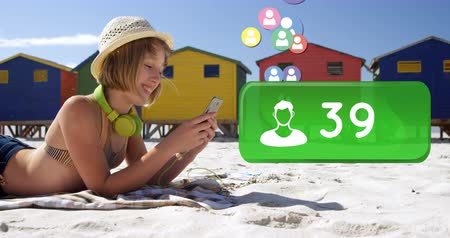 обмен сообщениями : Close up of a Caucasian woman lying on the beach wearing a bathing suit typing on her phone. Beside her in the foreground is a digital animation of a bar with a follower icon increasing in count and icons flying upwards 4k