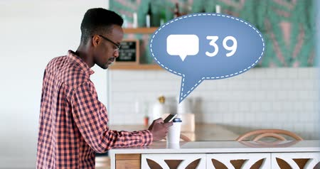 interaktif : Side view of an African-american man leaning on a kitchen counter sipping on a cup of coffee while texting. Beside him is a digital animation of a message bubble with a message icon increasing in count 4k Stok Video